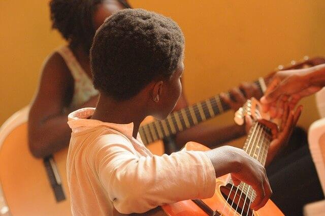 criança aprendendo a tocar violão